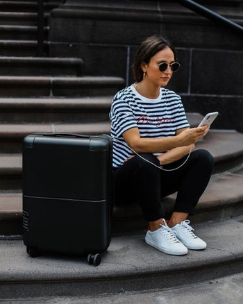 model sitting next to the black suitcase while charging a phone from it