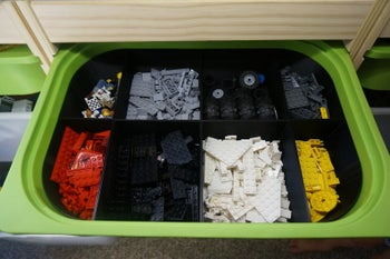 A storage bin within an Ikea Trofast bin with compartments containing legos sorted by color