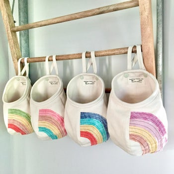 Four rainbow pods hanging on a shelf