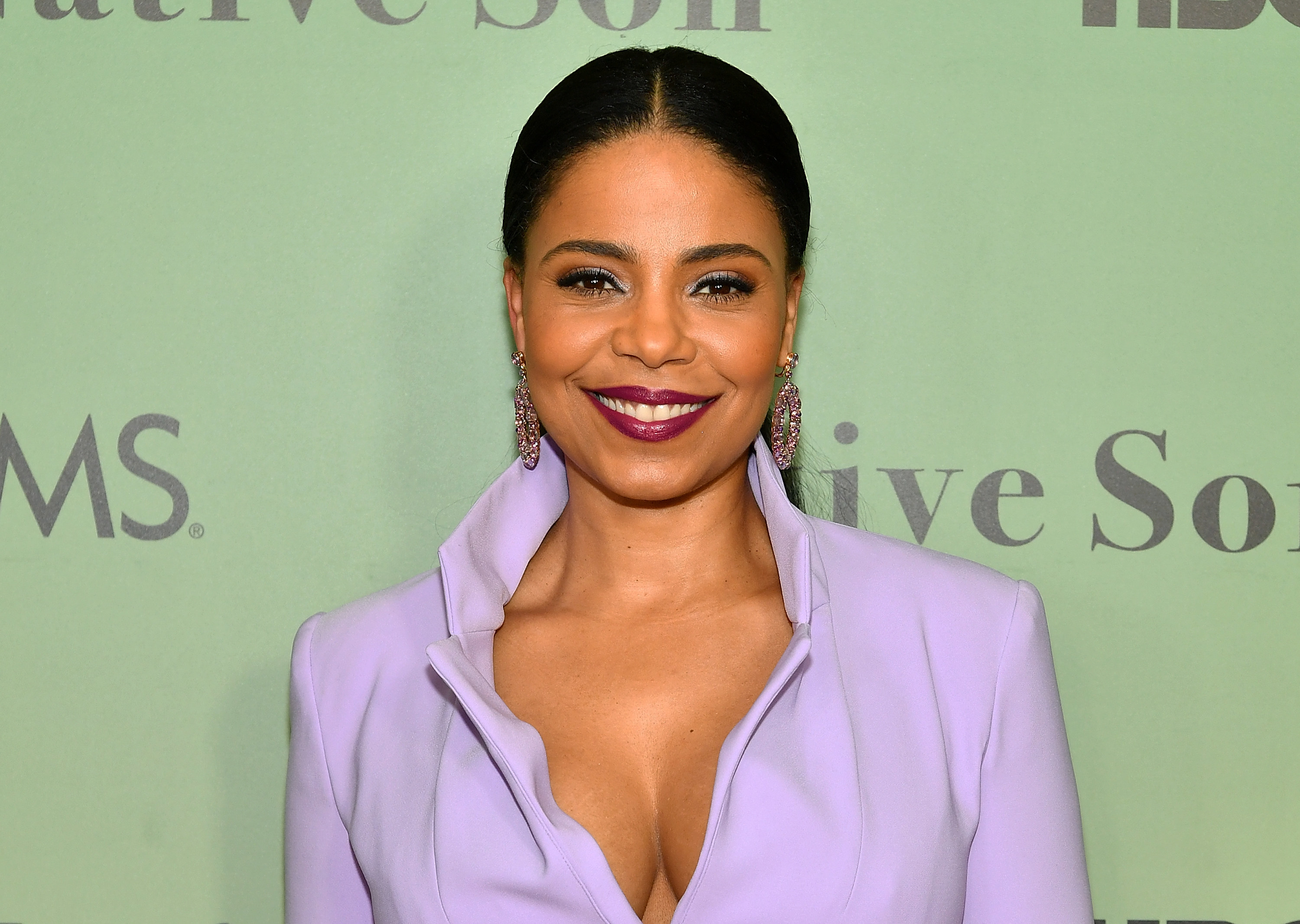 Sanaa wears a lilac collared blazer dress with a plunging neckline