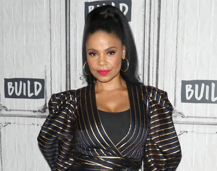 Sanaa wears her hair in a high ponytail and a black and gold striped dress