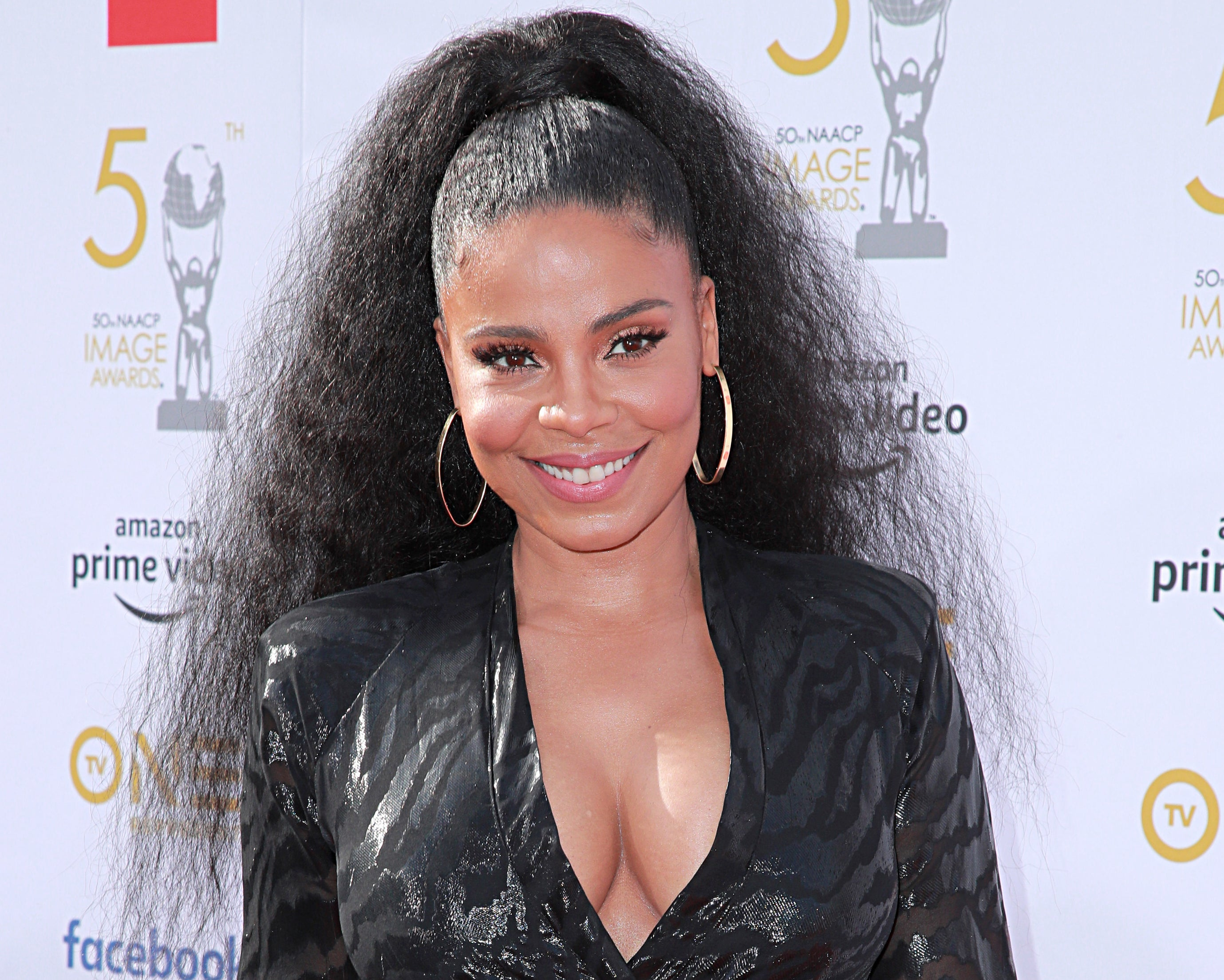 Sanaa wears her hair in a ponytail with gold hoop earrings and a black dress with a plunging neckline
