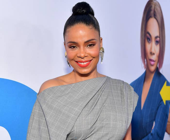 Sanaa smiles while wearing her hair in a bun and an off the shoulder grey and white plaid dress