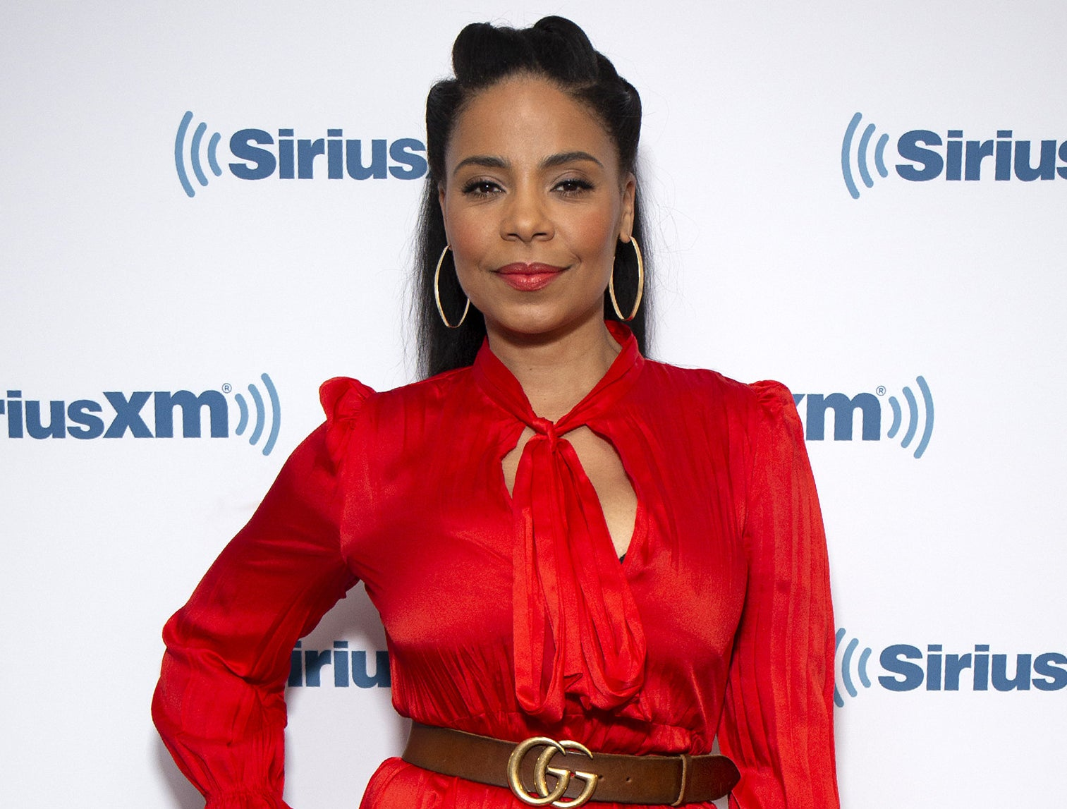 Sanaa wears a red dress with a keyhole neckline and brown Gucci belt