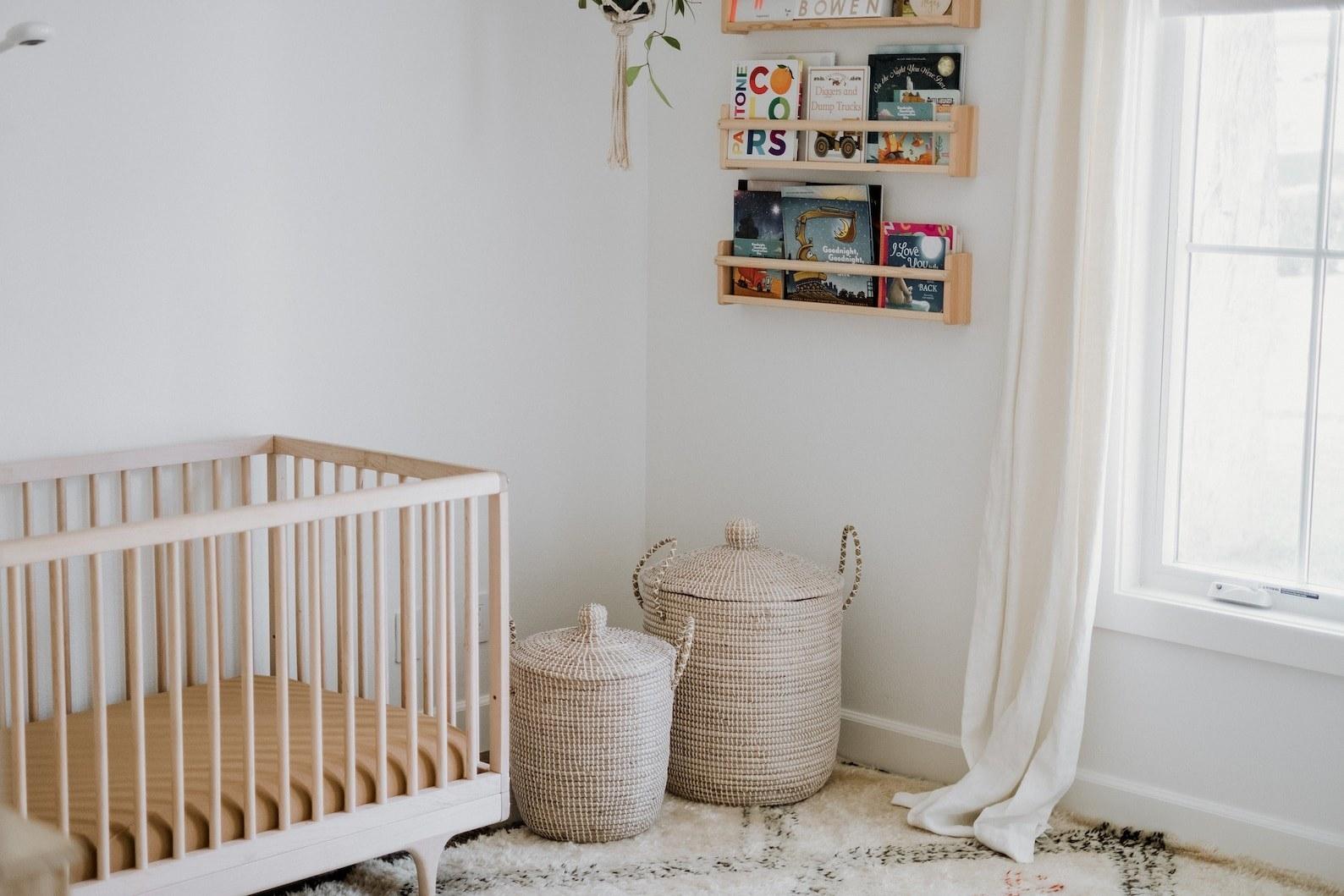 Two beige lidded wicker baskets in a nursery