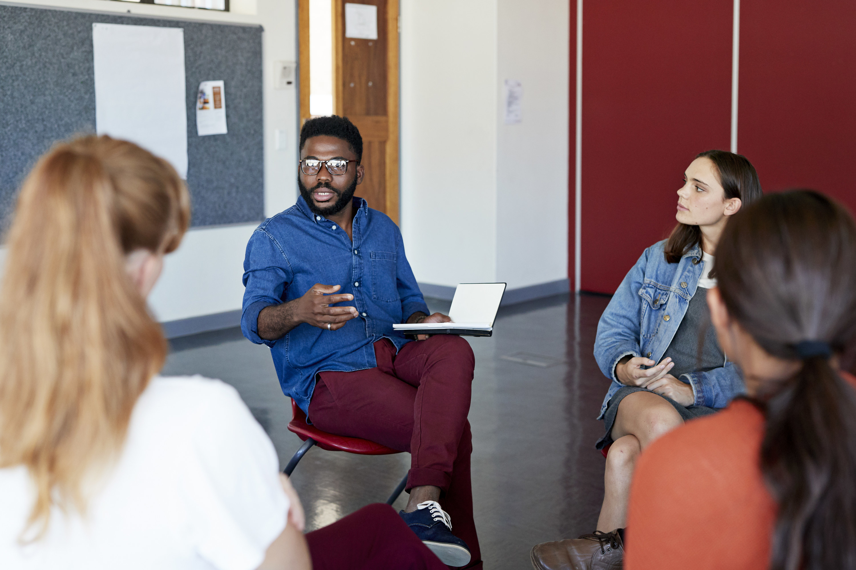 Professor talking with college students in a discussion group