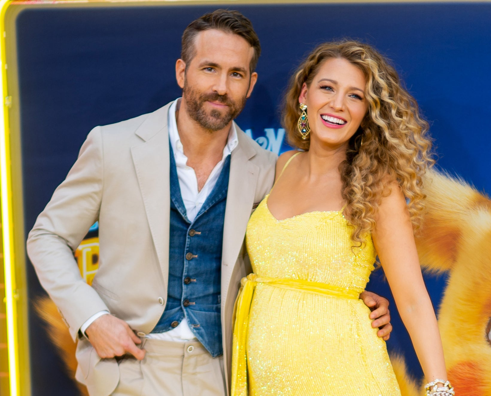 Blake wears a sequined yellow gown while posing with Ryan