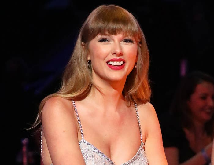 Tayor smiles while wearing a silver top with crystal straps