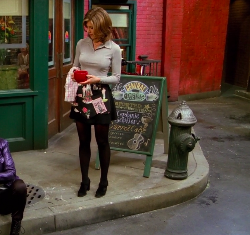 Rachel wearing small booties, tights, a skirt, an apron, and a long-sleeve shirt with a collar like a blazer