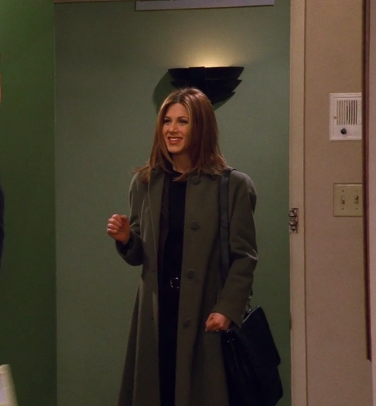 Rachel wearing pants, a shirt, a blazer, a large coat, and she has a briefcase