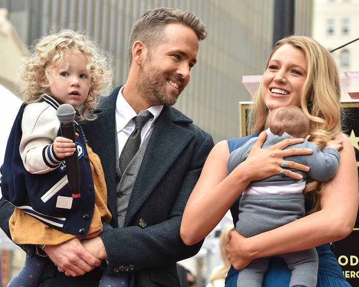 Ryan smiles at Blake while they hold two of their children
