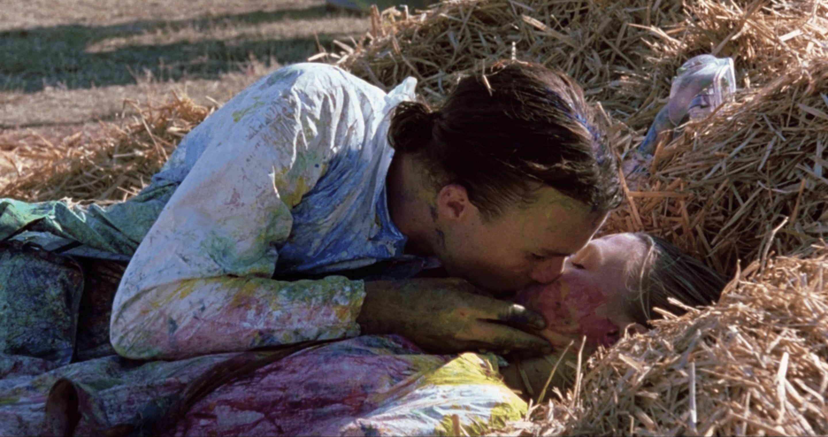 Kat and Patrick kiss in the hay after a game of paintball