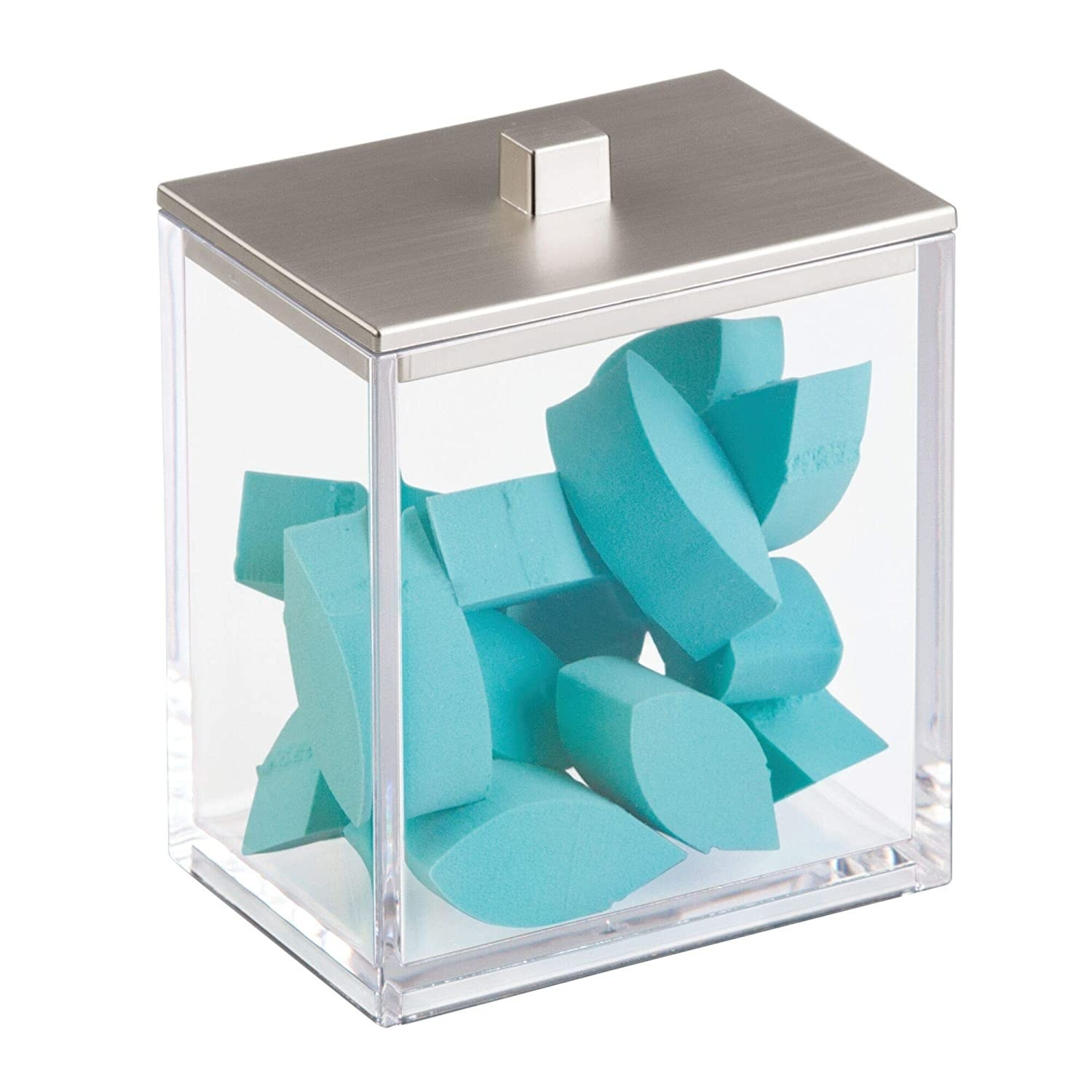 A clear canister with makeup sponges inside having a silver lid and trimmings