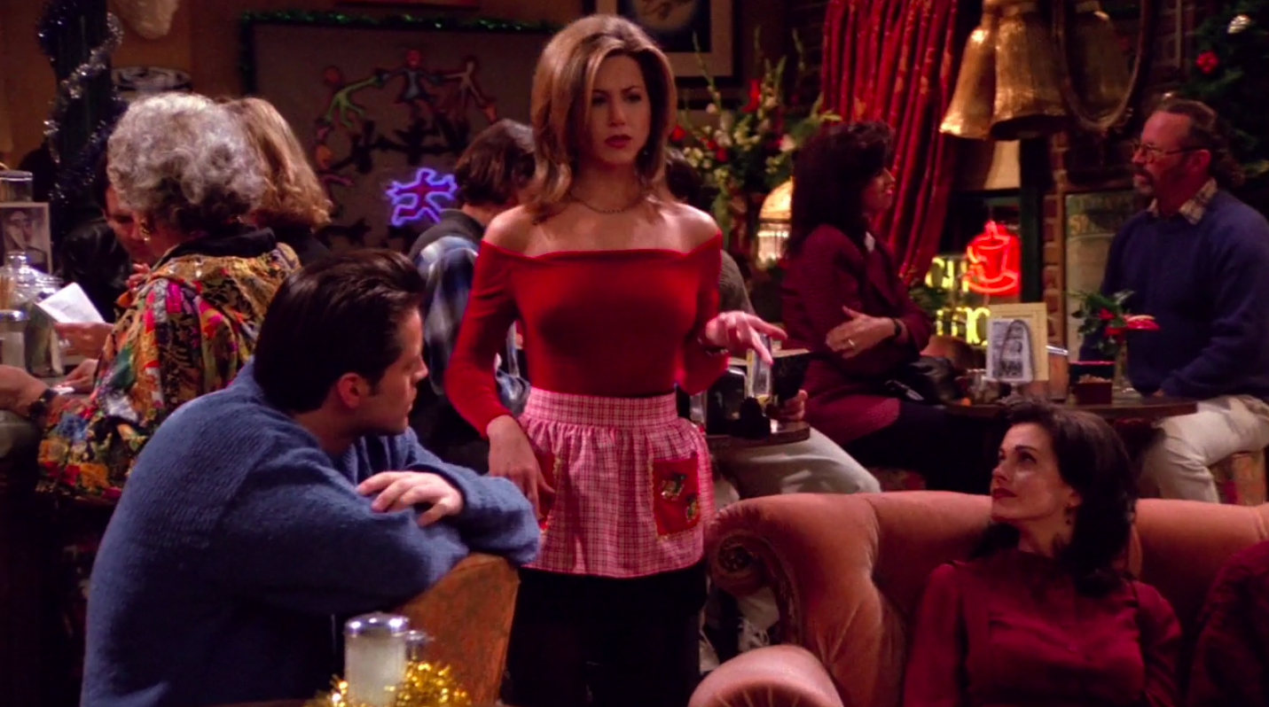 Rachel wearing booties, tights, a skirt, an apron, an off-the-shoulder long-sleeve shirt, and a necklace