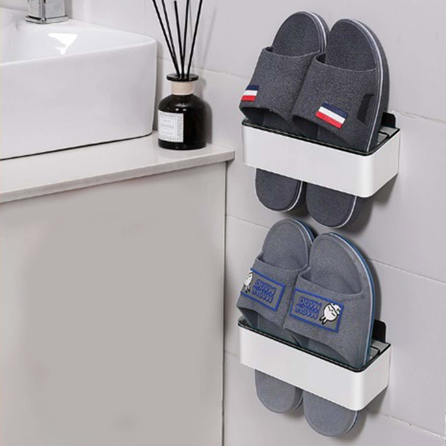 A set of 2 wall mounted bathroom racks in white & black with flip flops hung on them