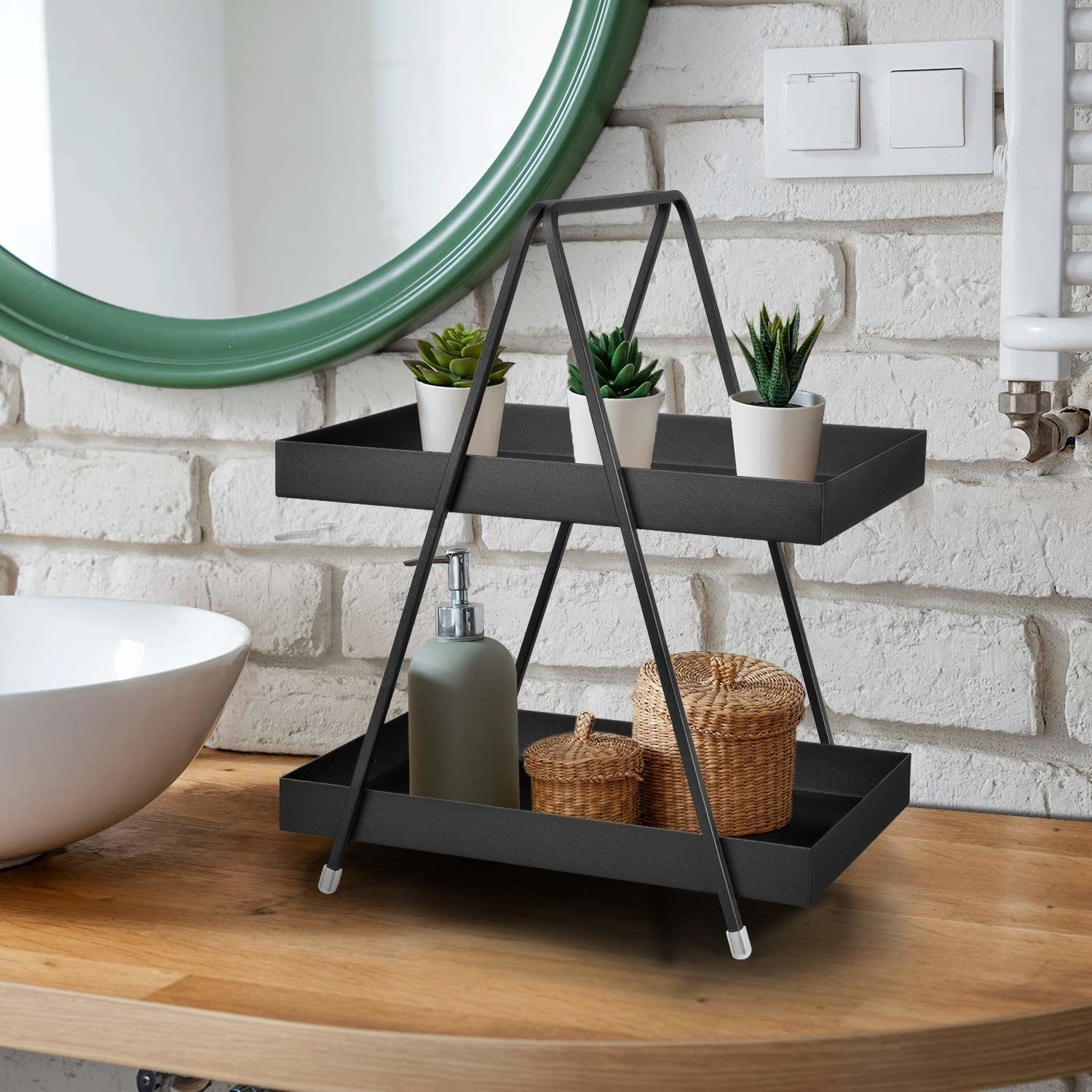 A black 2-tier standing rack made from metal and holding potted plants and baskets