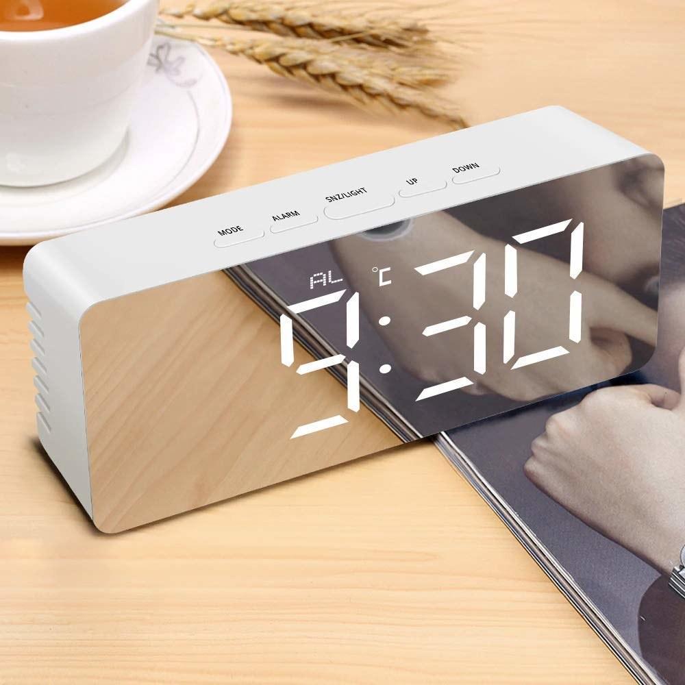 A rectangular silver digital alarm clock