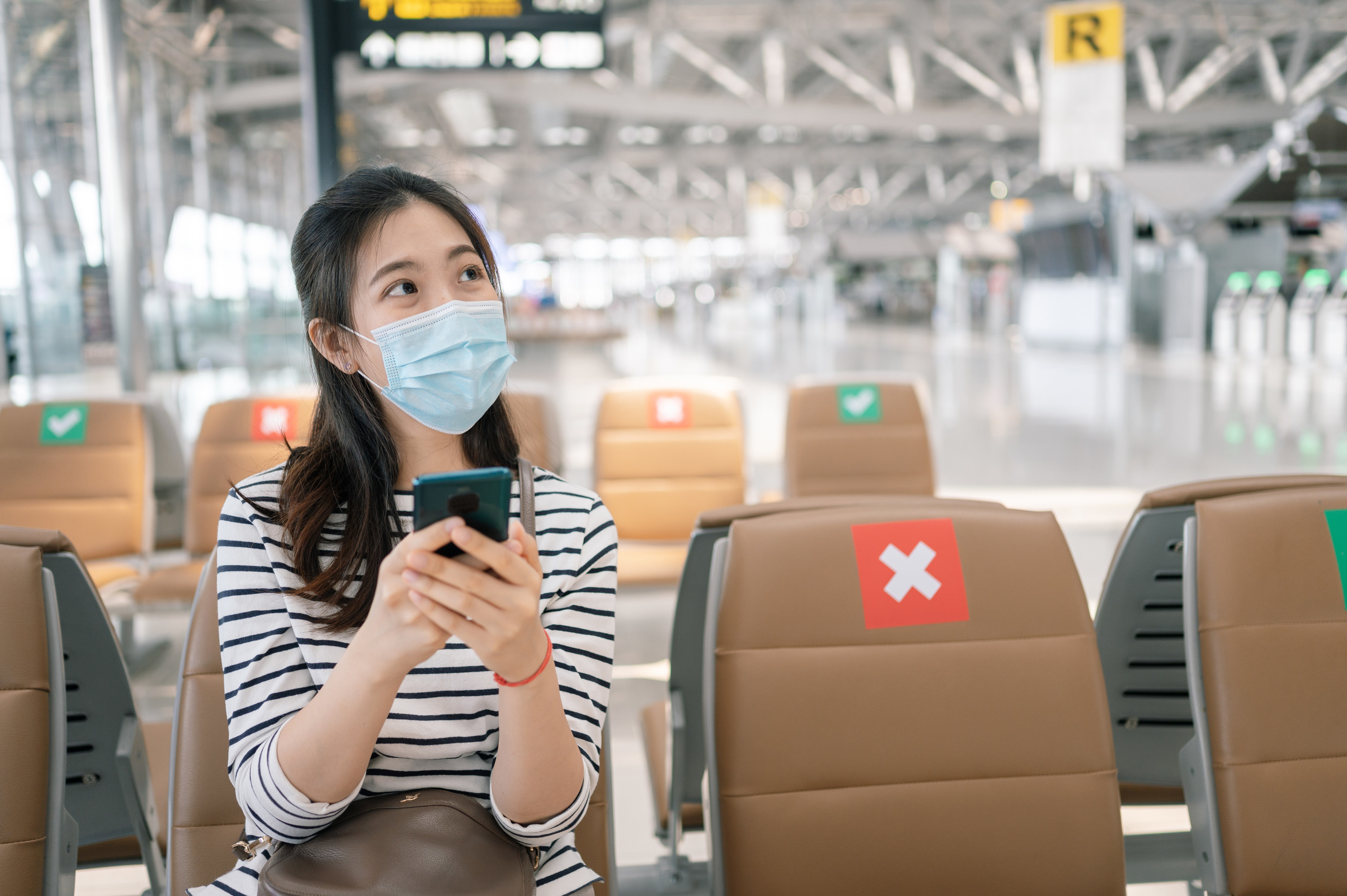 Woman in airport looking at her phone