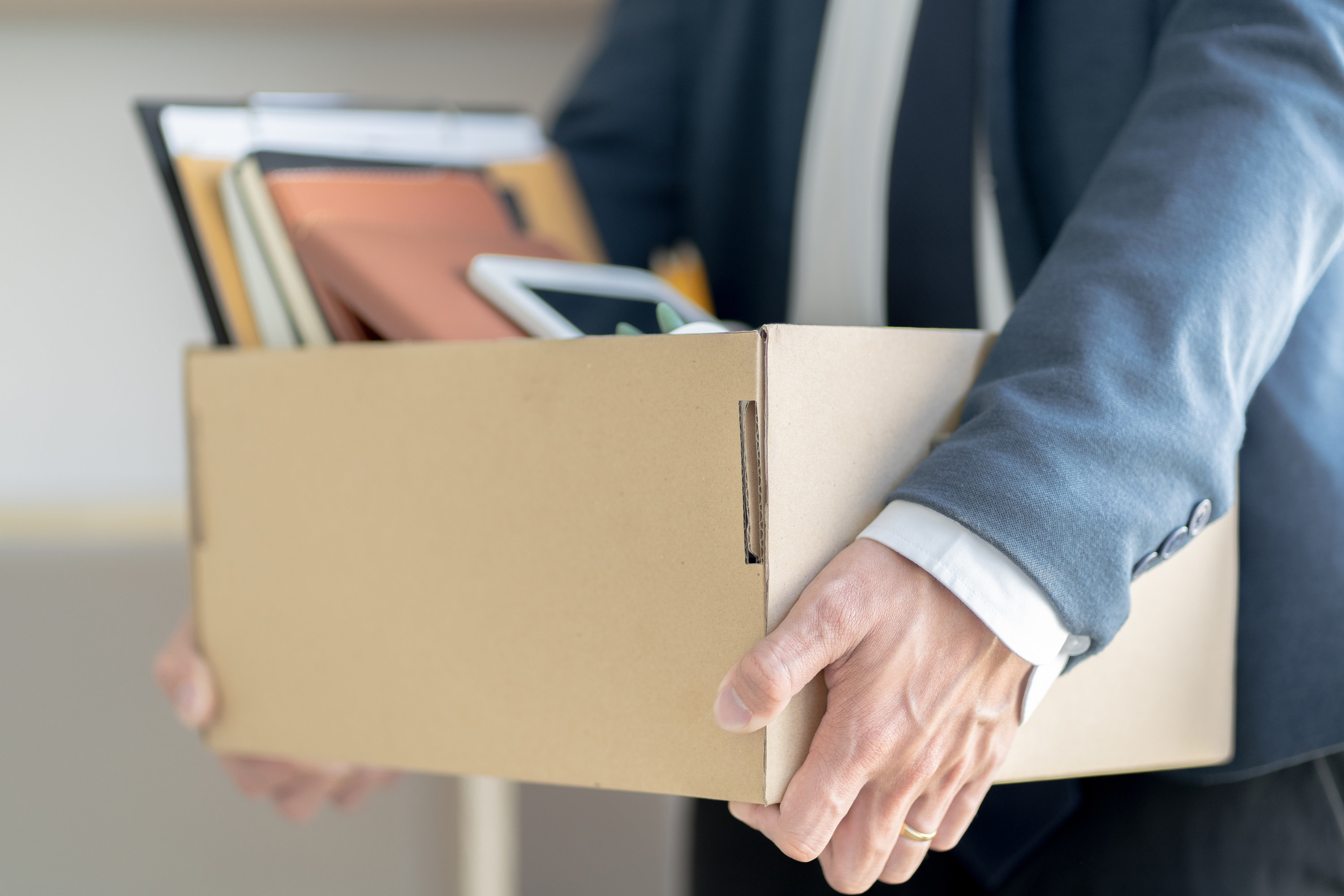 Person carrying a box of their things out of the office after being fired