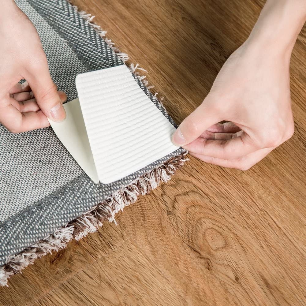 A person applying a gripper to the back of their rug
