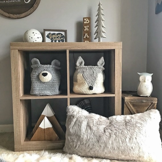 The grey crochet fox basket displayed in a wooden cube storage unit in a nursery