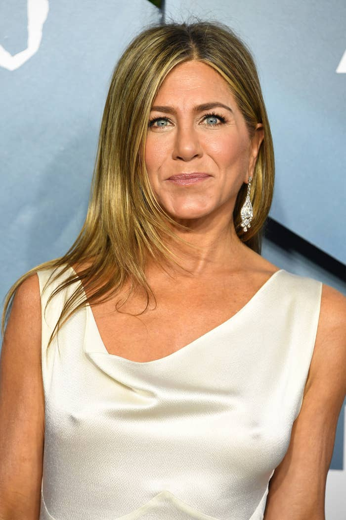 Aniston poses in a dress at a red carpet event