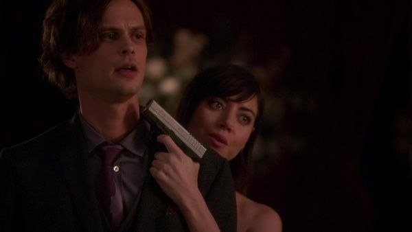 Cat holding a gun up to Spencer's head