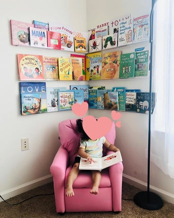 Reviewer's photo showing their child's books displayed on the invisible floating shelves attached to the wall