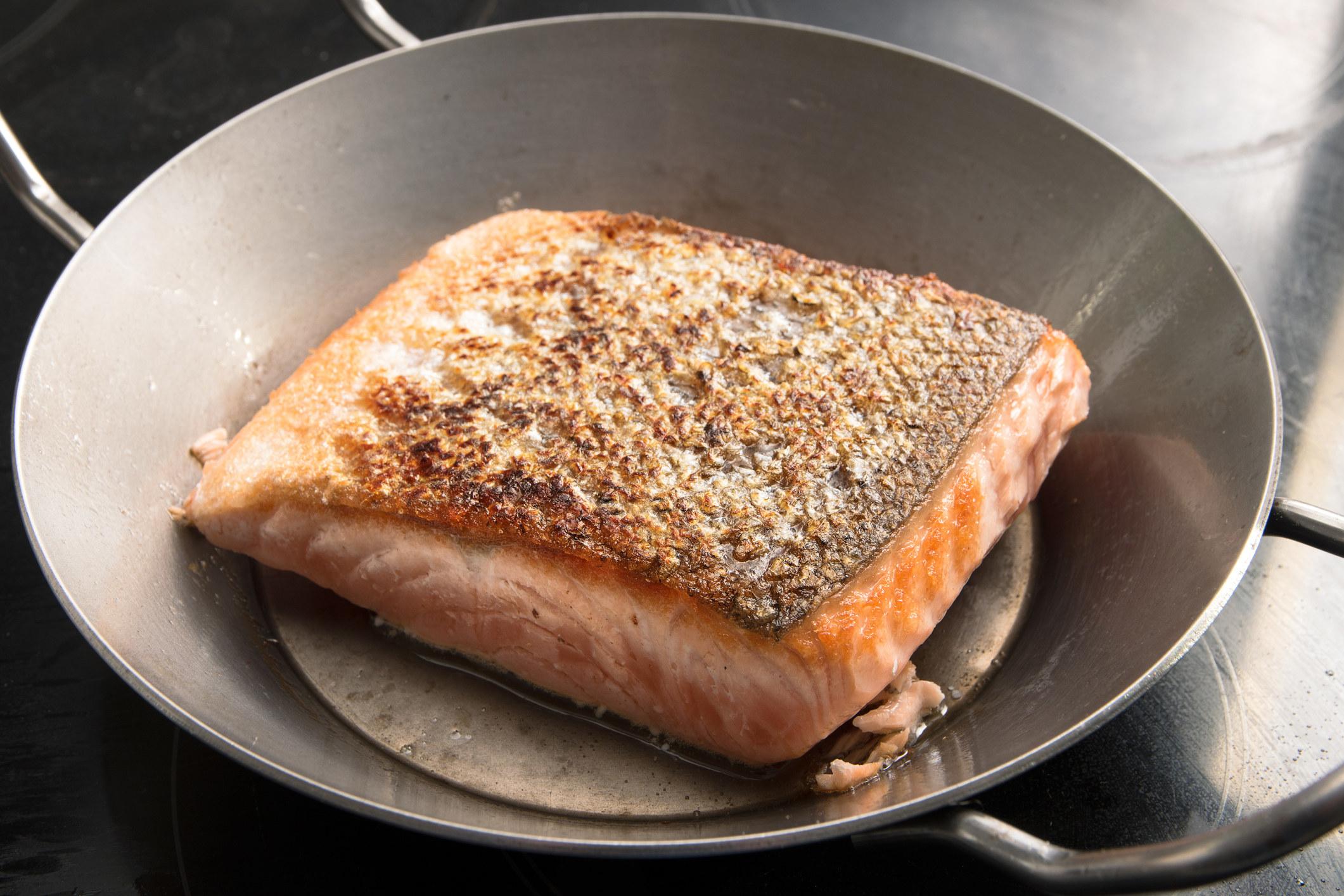 Crispy salmon skin in a pan.
