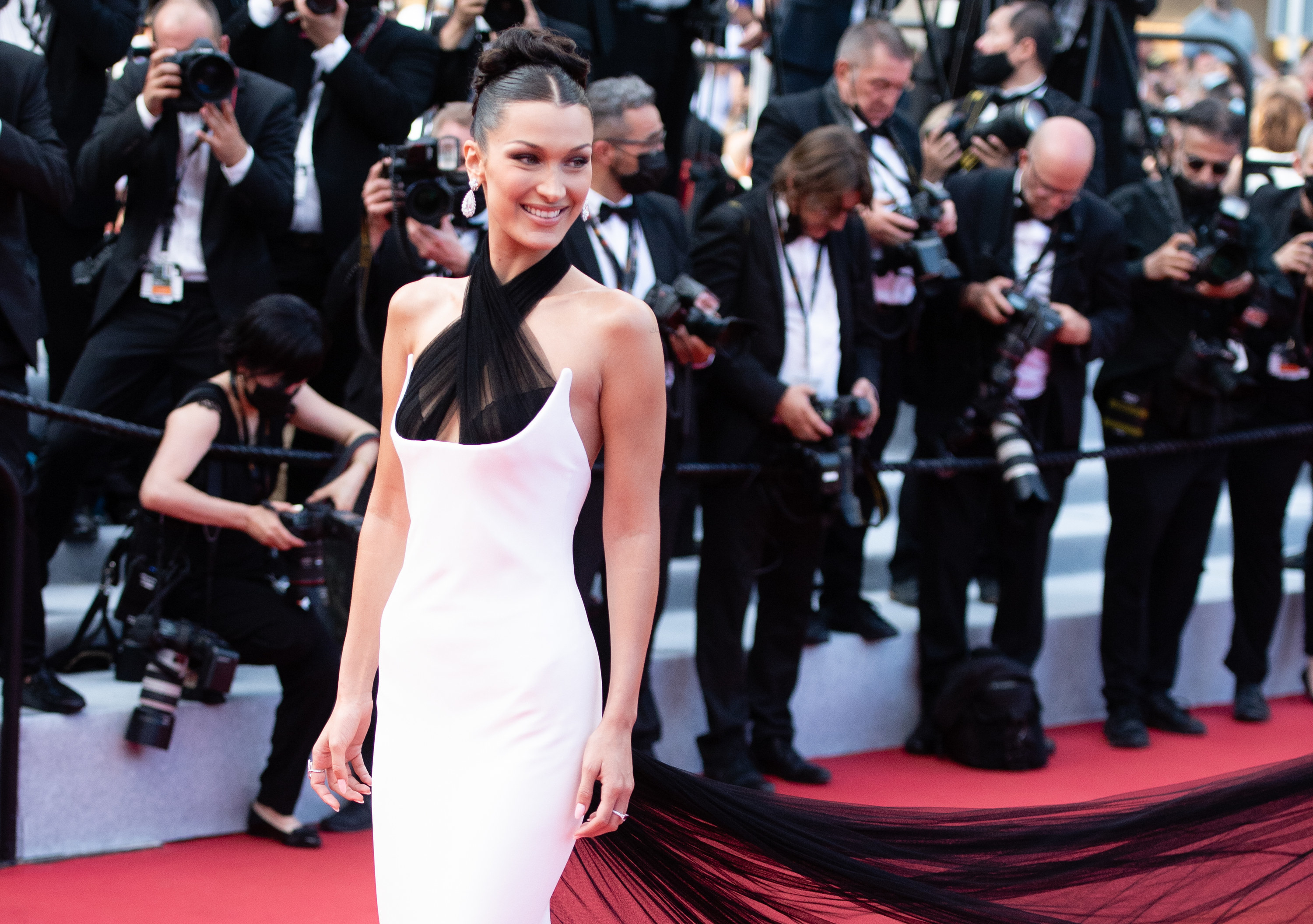Bella Hadid is photographed smiling on the red carpet at the Cannes Film Festival in 2021