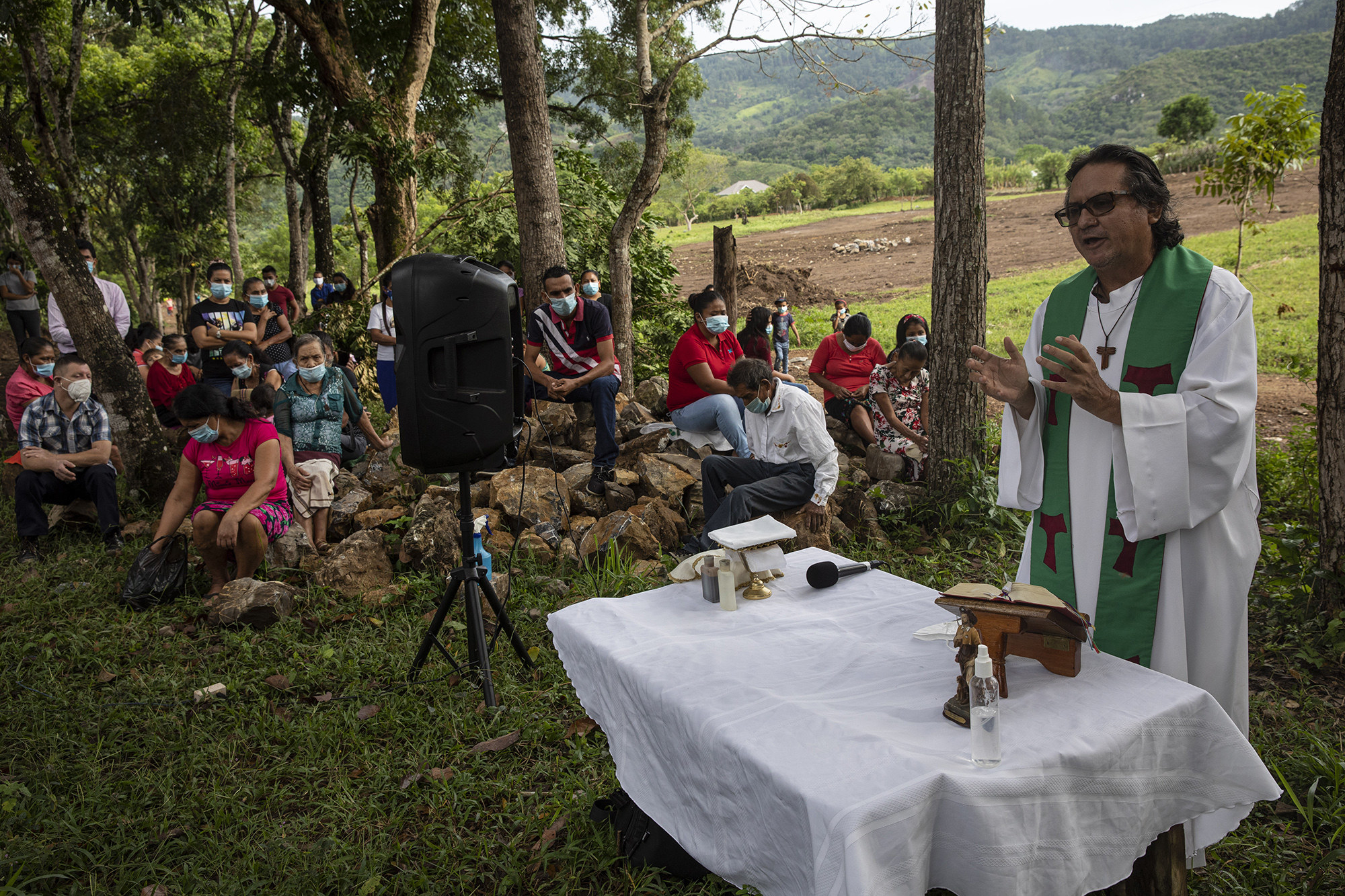 Friar Leopoldo Serrano stands at a table with a white cover to celebrate an outdoor Mass at Mission San Francisco de Asis in Honduras on June 27; a number of people wearing masks sit nearby