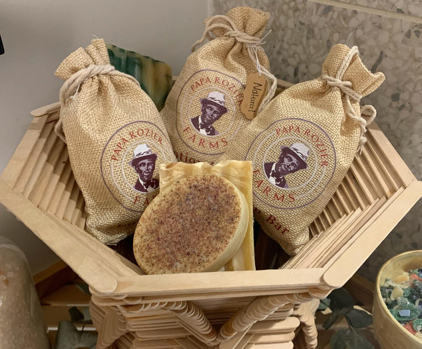 a lotion bar surrounded several others in burlap drawstring packaging
