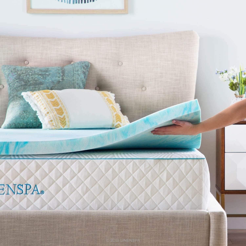 A person lifting the mattress pad