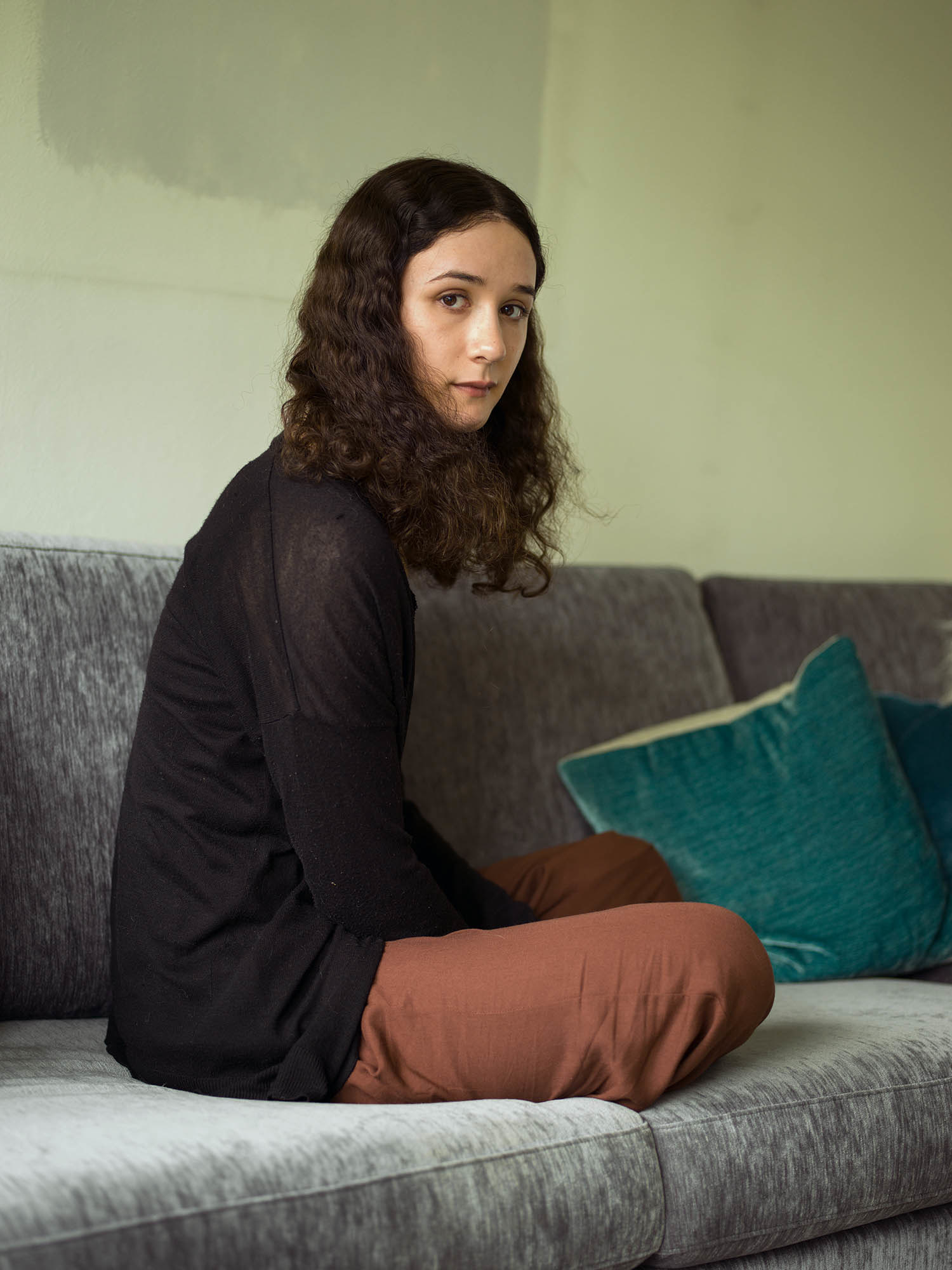 A person sits on a couch with their legs crossed and gazes at the camera