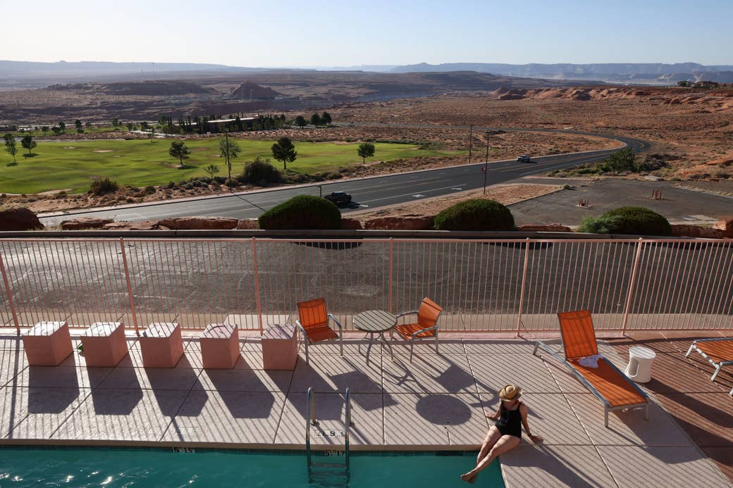 A woman sunbathes next to a swimming pool overlooking a golf course and Lake Powell in Arizona