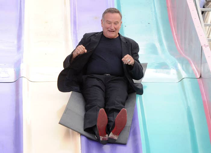 Robin Williams goes down a slide at a movie premiere