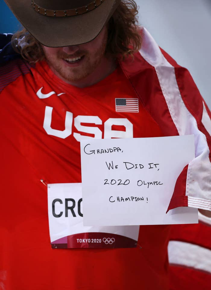 """Ryan holds up a sign that says, """"Grandpa, We did it, 2020 Olympic Champion!"""""""