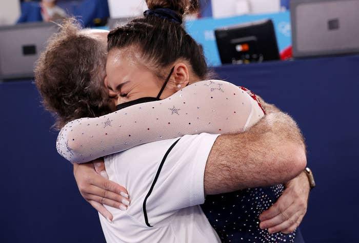 Suni being hugged by a coach