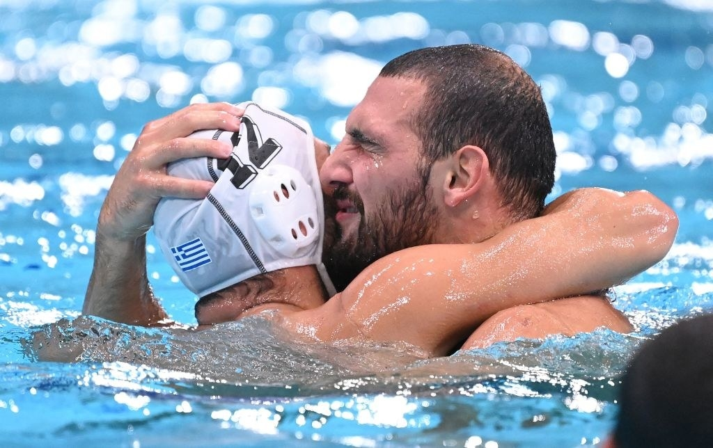The Greek athletes hugging each other in the water
