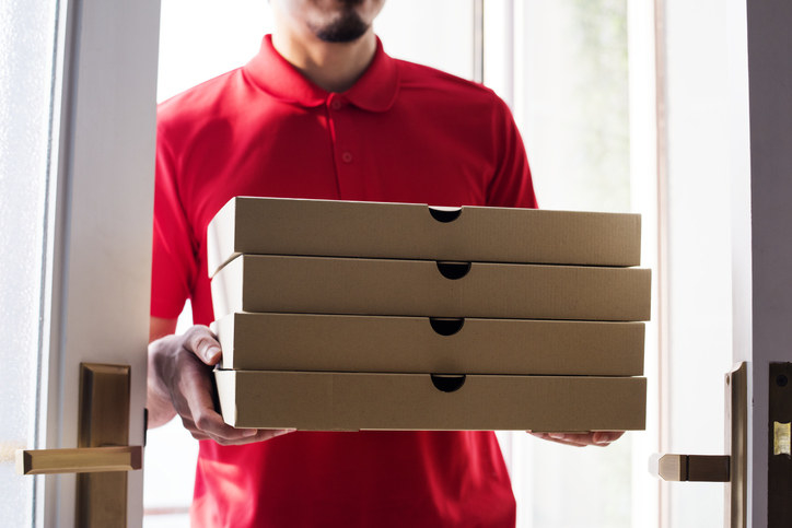 Pizza delivery man holding boxes of pizzas