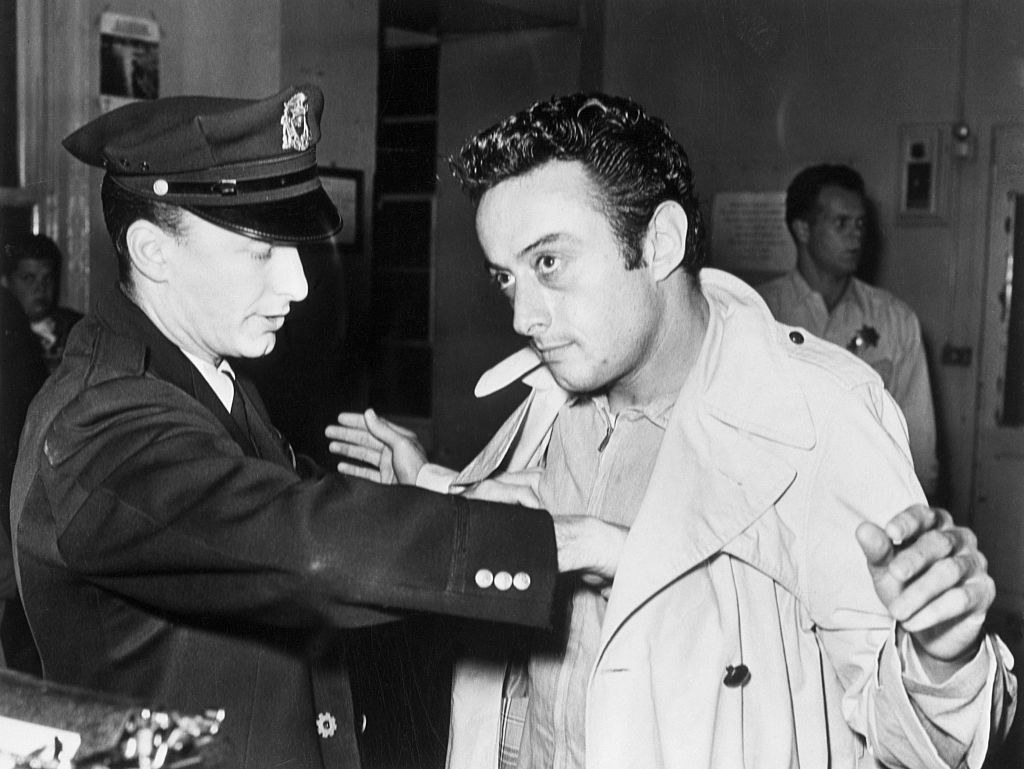 Lenny Bruce getting searched by a police officer after being arrested