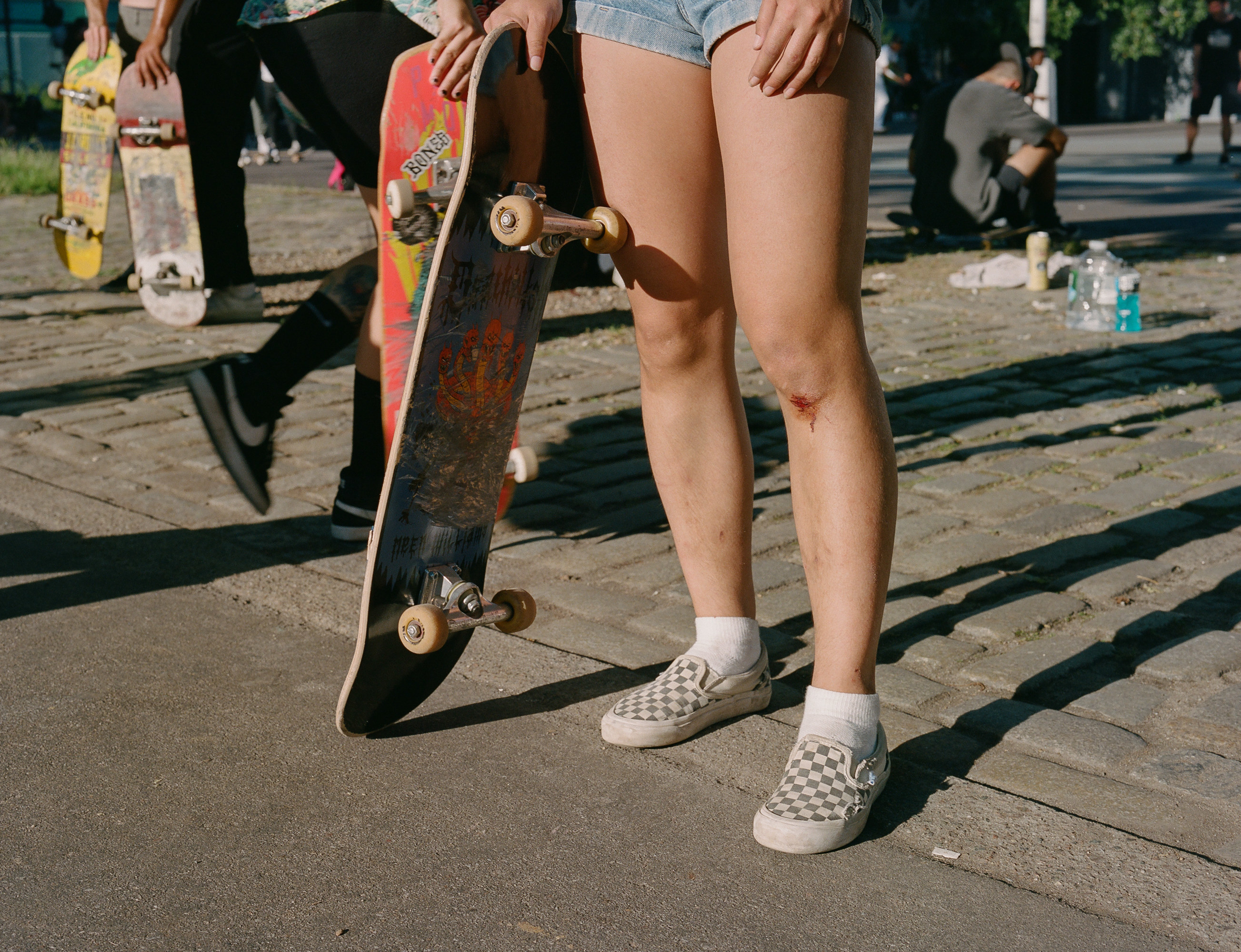 A woman with a cut knee and a skateboard