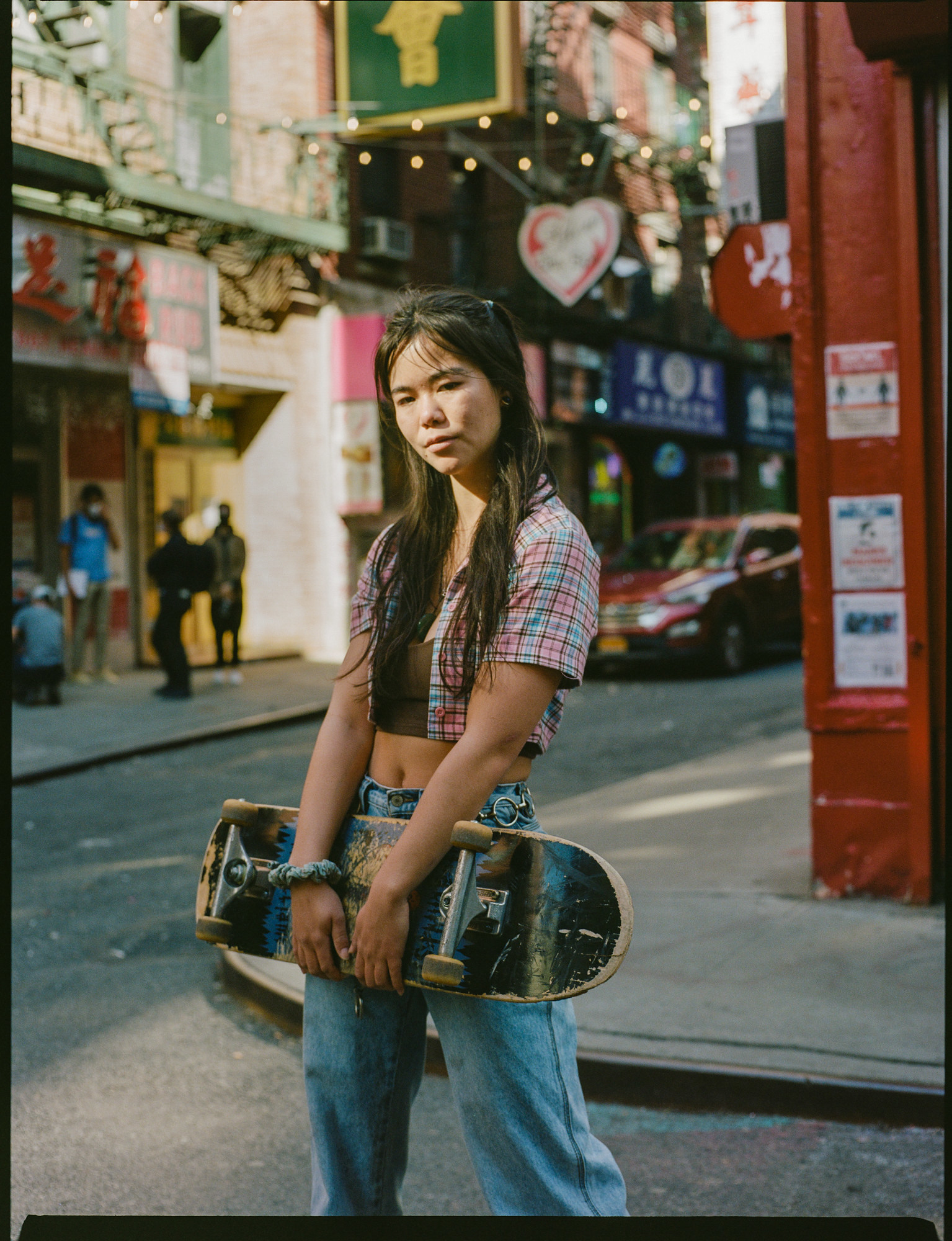 A woman in a crop top and jeans holds a skateboard