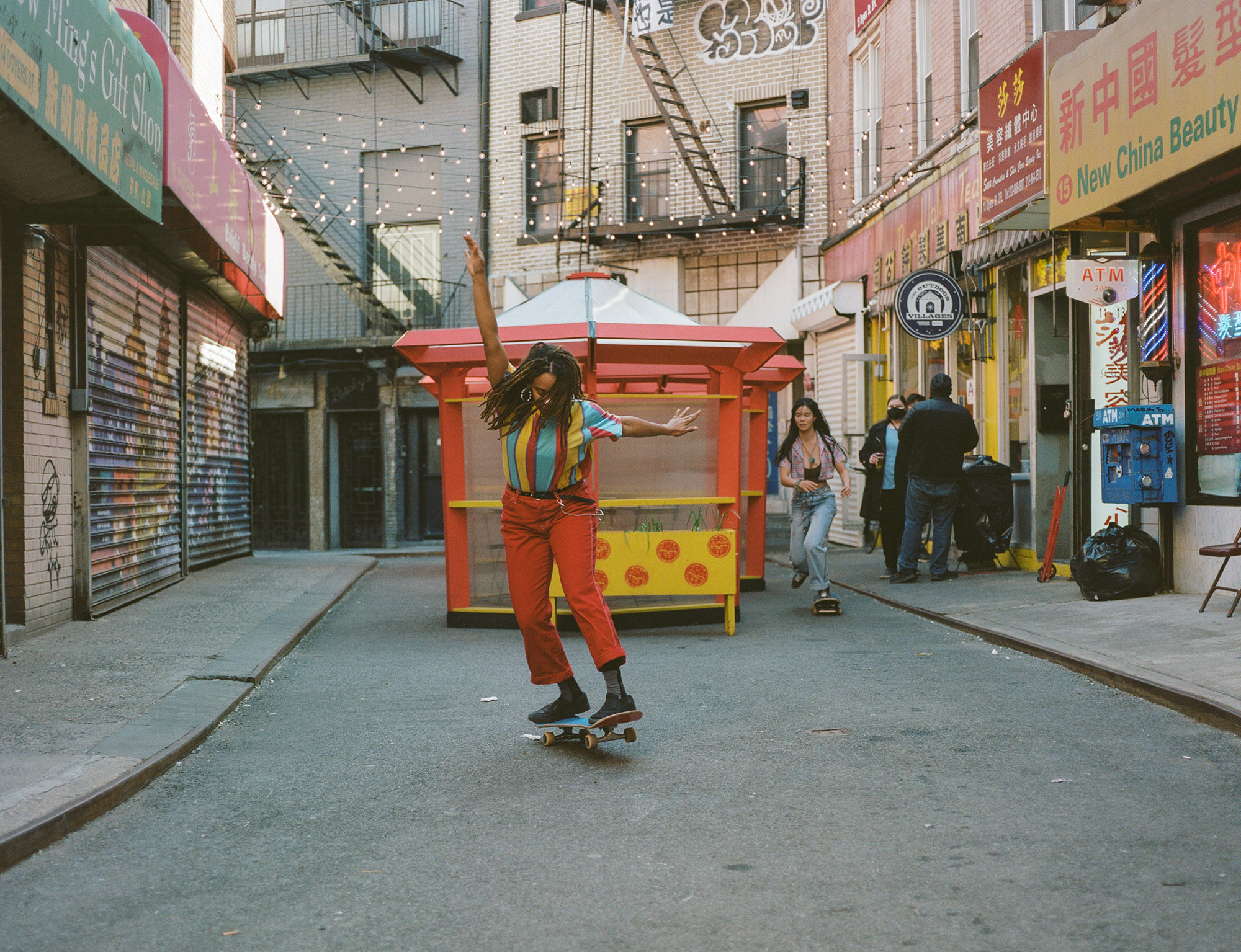A woman doing a trick on a skateboard on the street
