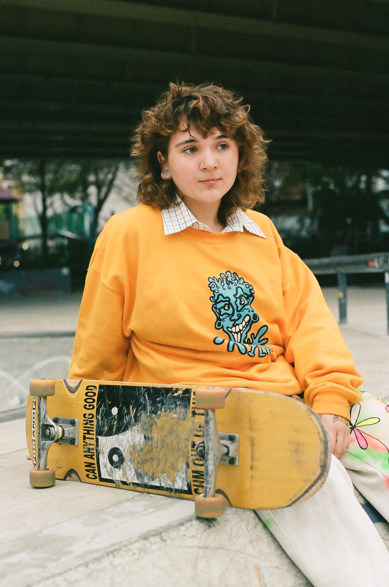 A woman with a yellow sweatshirt and a yellow skateboard