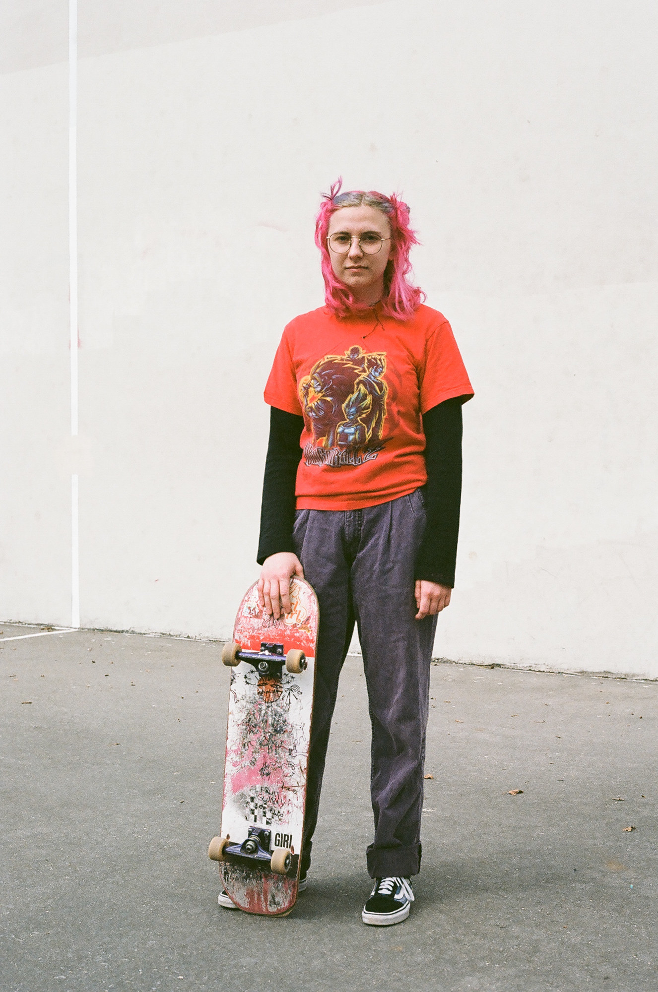 A woman with pink hair stands with a pink skateboard