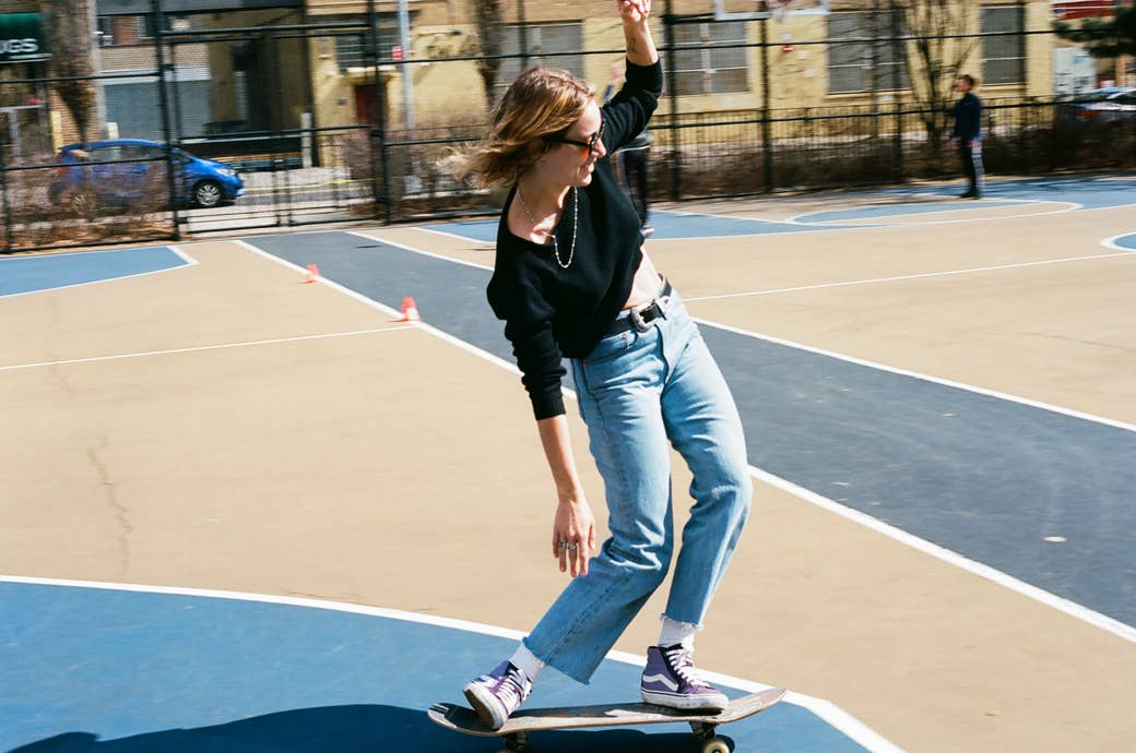 A woman on a skateboard with her hands up