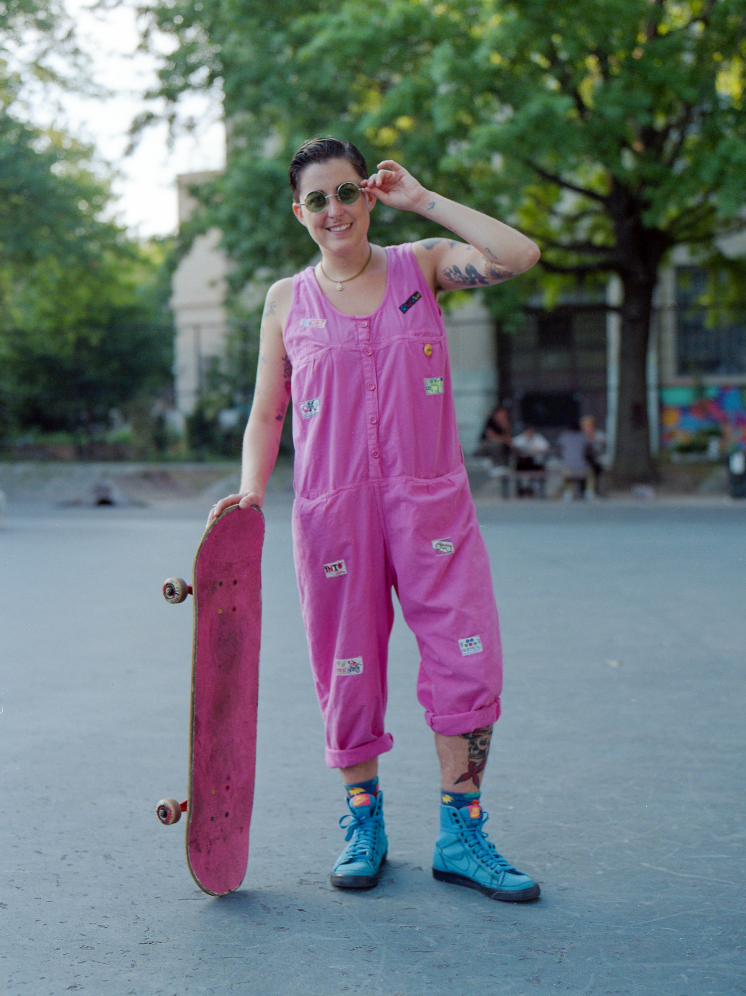 A woman in an all pink romper with blue sneakers and a skateboard that is painted pink