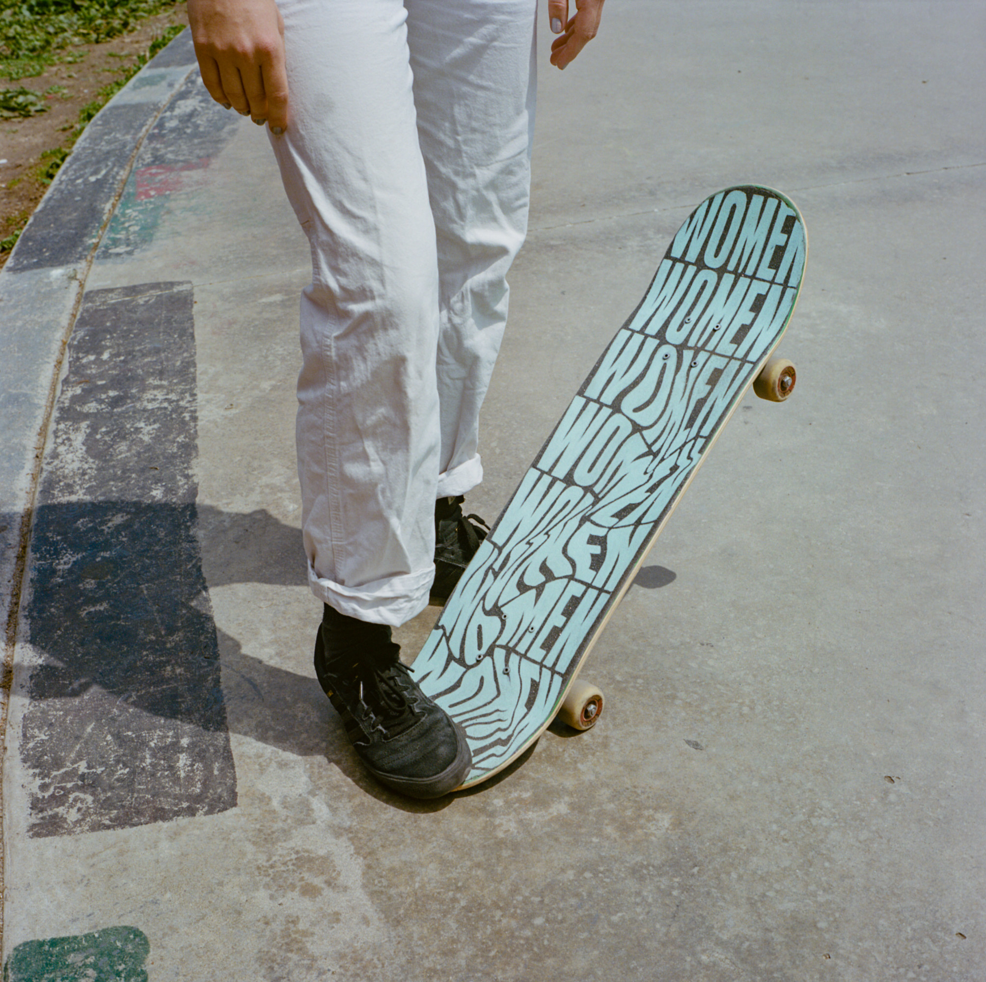 """A woman with one foot on a skateboard that says """"women"""" all over it"""