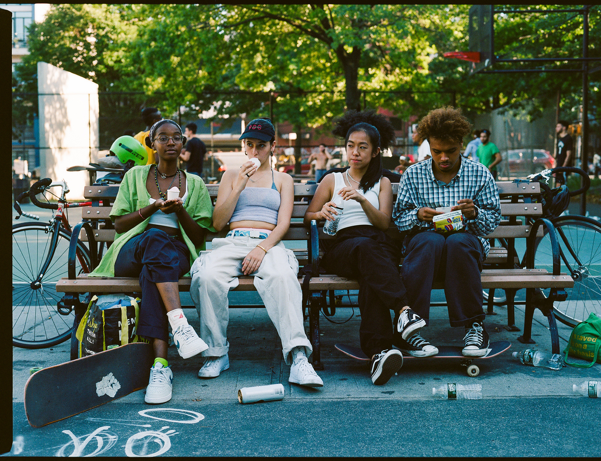 A group of women sitting on a park bench eat a snack with skateboards at their feet